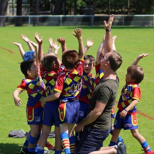 Educateur et enfants rassemblés en cercle et levant les main au ciel.