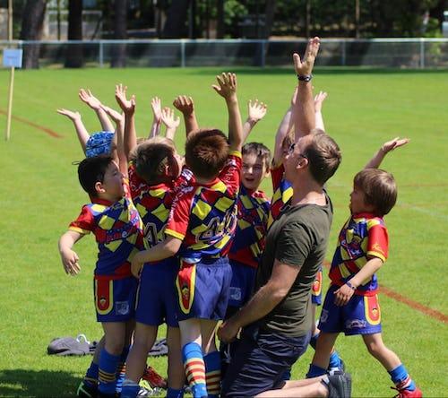 Des enfants autour de leur éducateurs levant les mains vers le ciel