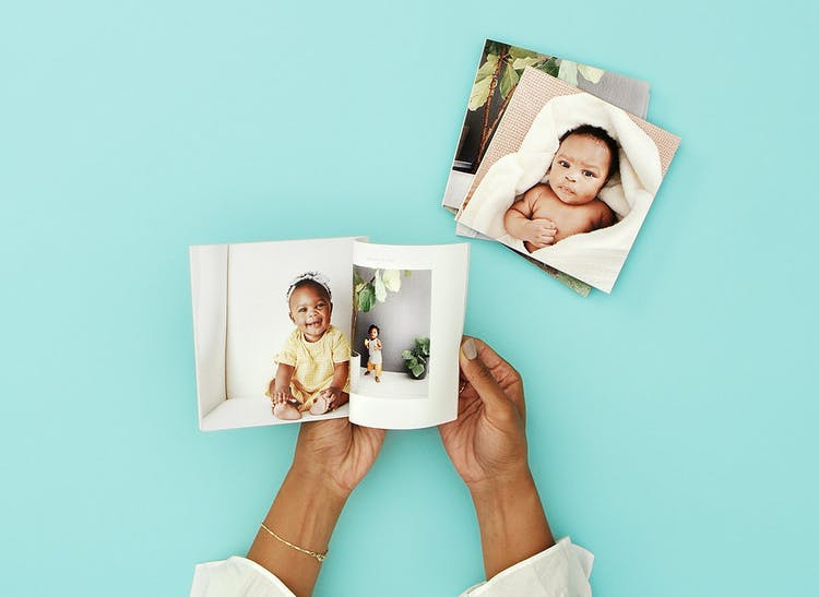 hands opening photo book with baby on pages and stack of softcover photo books nearby