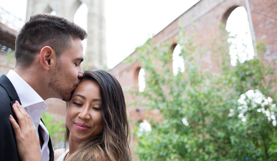 husband kisses his wife on the forehead while they pose in front of a brick building