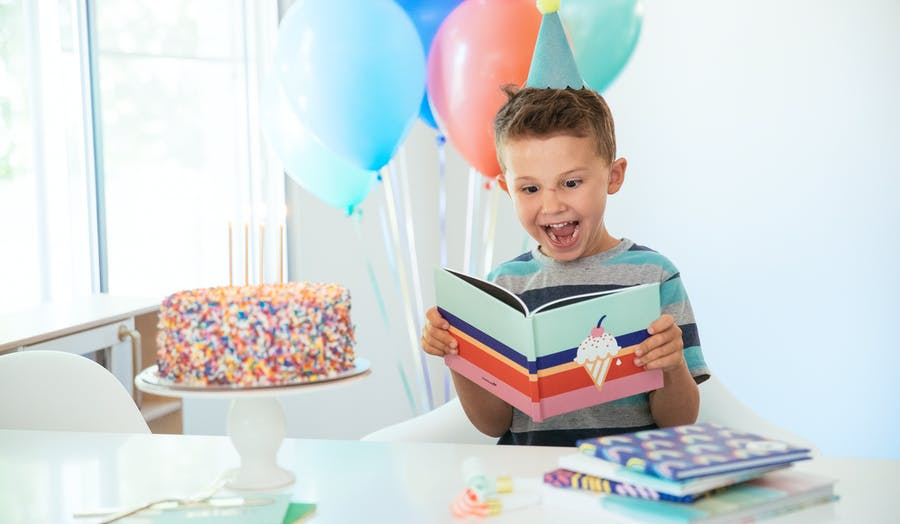 Little boy looking at a Chatbook with balloon and a cake around him.