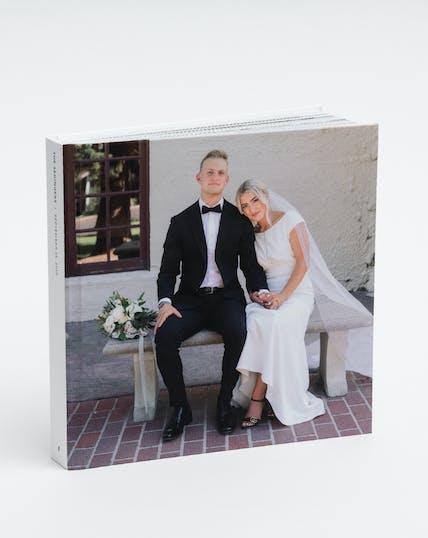 wedding photo album of couple sitting on bench on wedding day