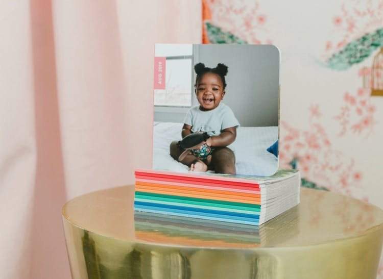 Stack of monthly photo books with baby on the cover on gold side table