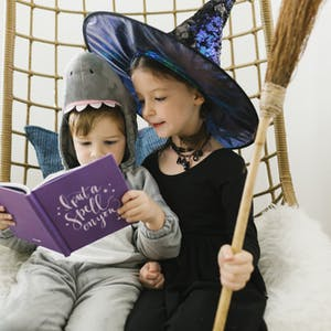 Brother and sister are dressed up for Halloween and looking through a Halloween Chatbook