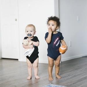 baby brothers posing for photo in sports onesies