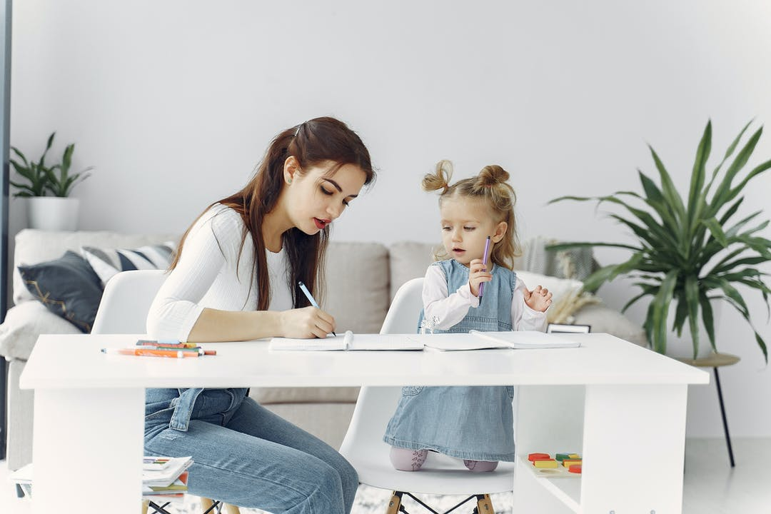 stressed mom with daughter writing down tips