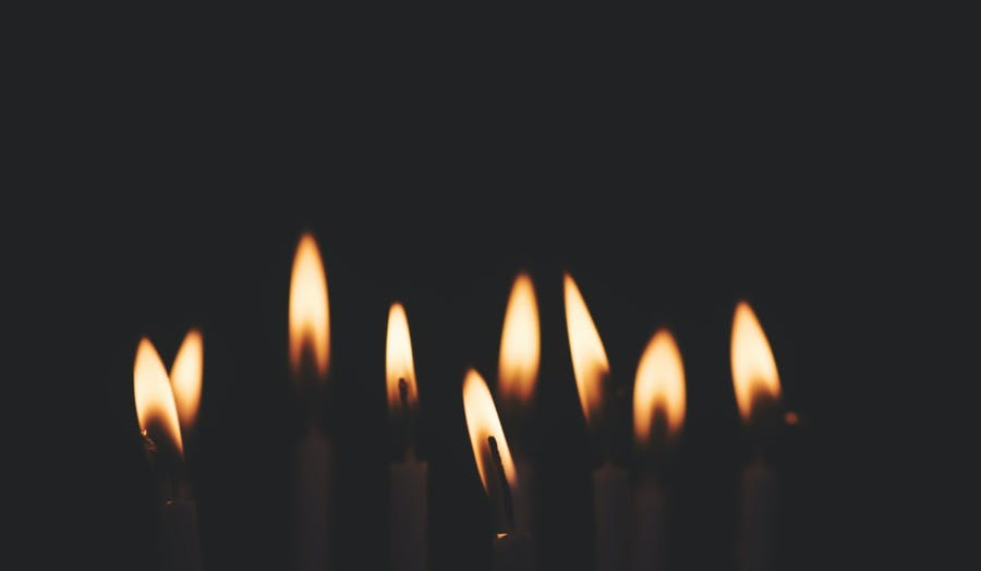 9 Candles are lit in a dark room for Hanukkah