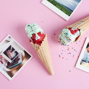 2 Ice Cream Cones and Photo Prints Scattered on Pink Paper