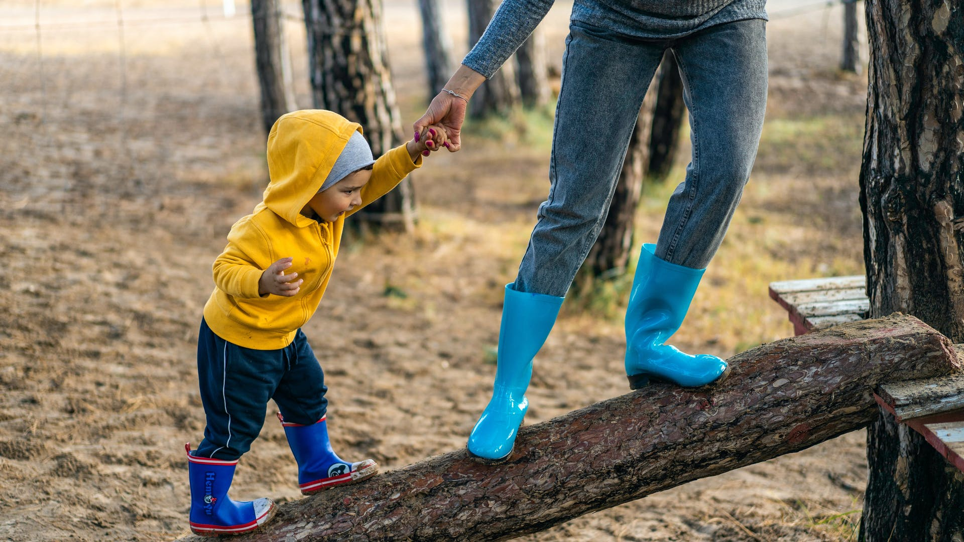 Mother leads a baby in boots up to a treehouse
