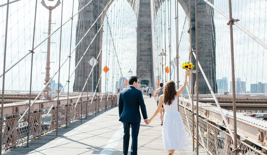 bride and groom walking across the Brooklyn bridge hand in hand