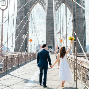 bride and groom walking across the Brooklyn bridge hand in hand