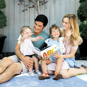 family outside on blanket reading alphabet book