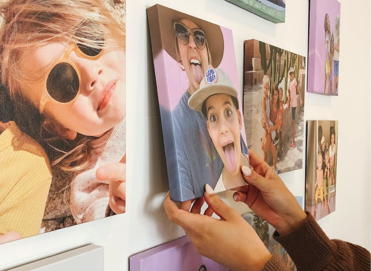 hands placing stickable photo tile on gallery wall of photo tiles
