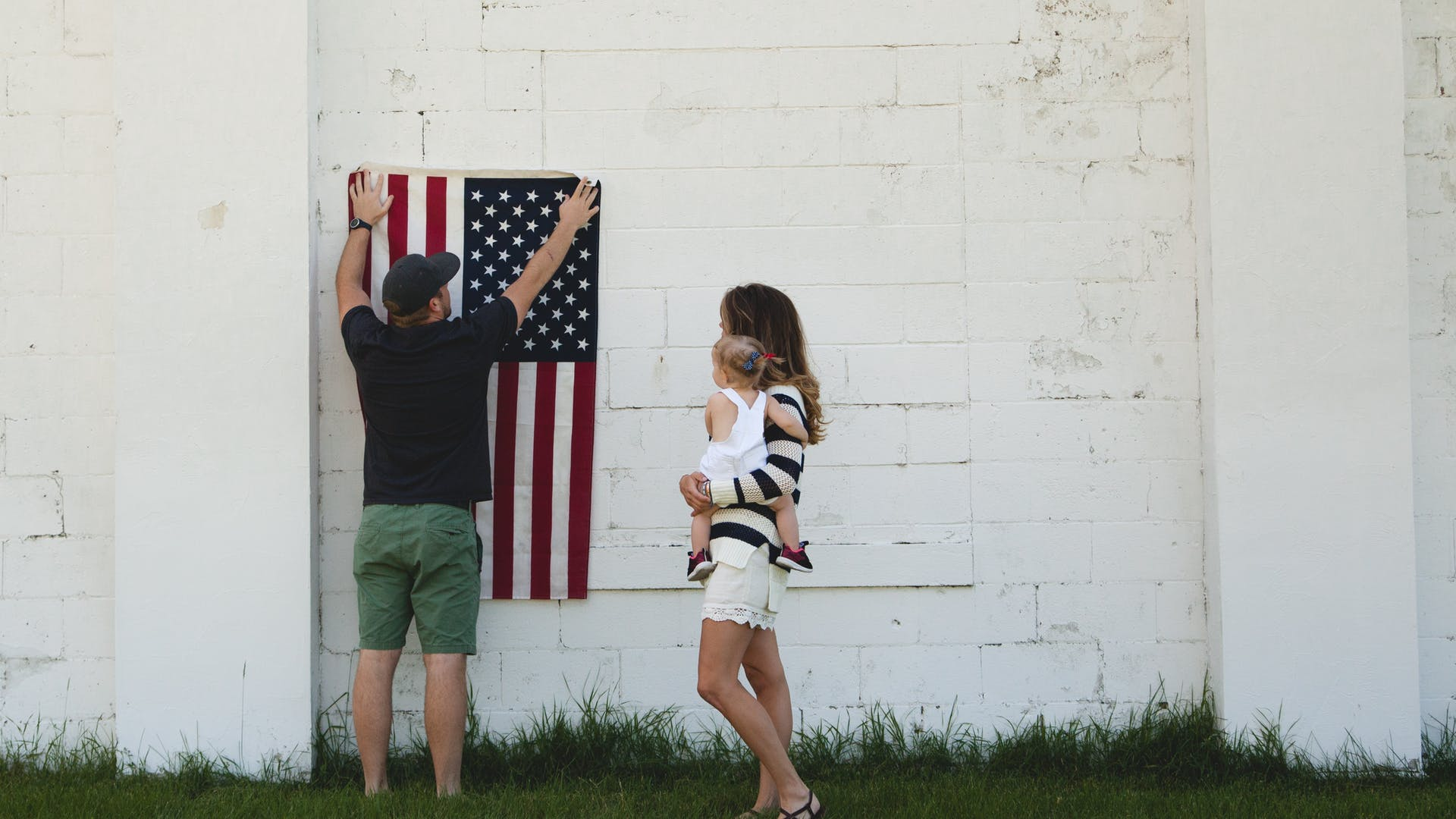 Father hangs up American Flag with family