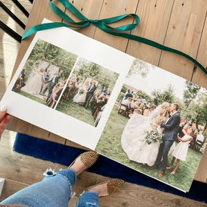 open wedding photo album showing couple kissing at altar