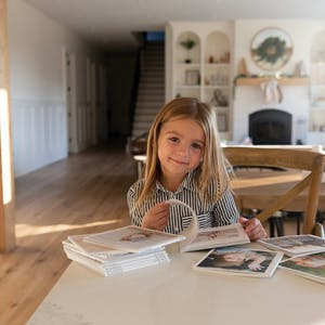 little girl flipping through monthly photo books at kitchen table