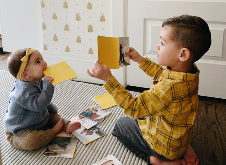 little boy showing monthly photo book to baby sister in nursery