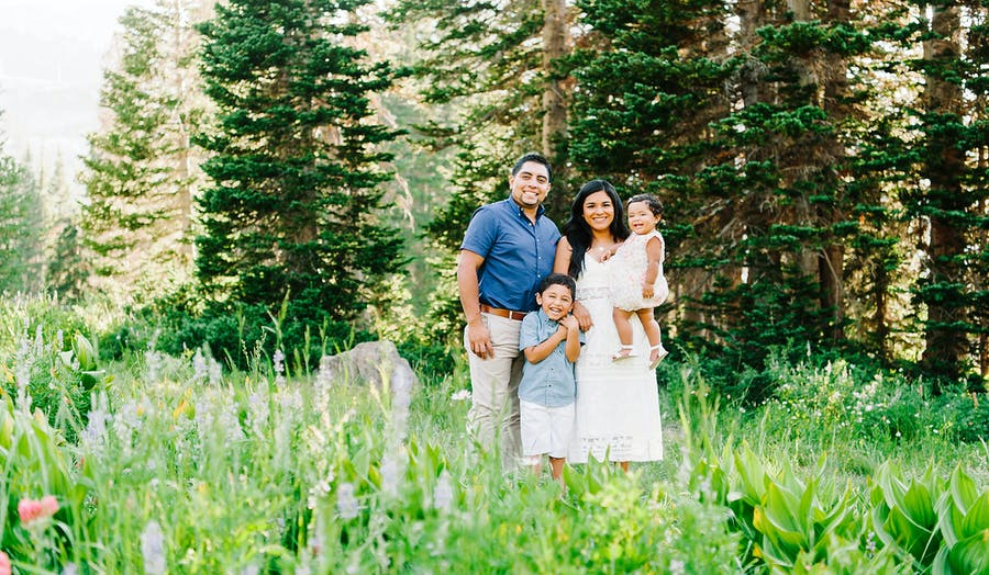 Family poses for family photos in a field of flowers and trees