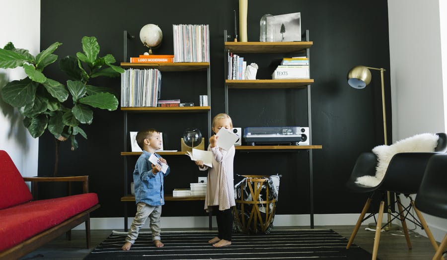 2 siblings play in their front room with Chatbooks photo books