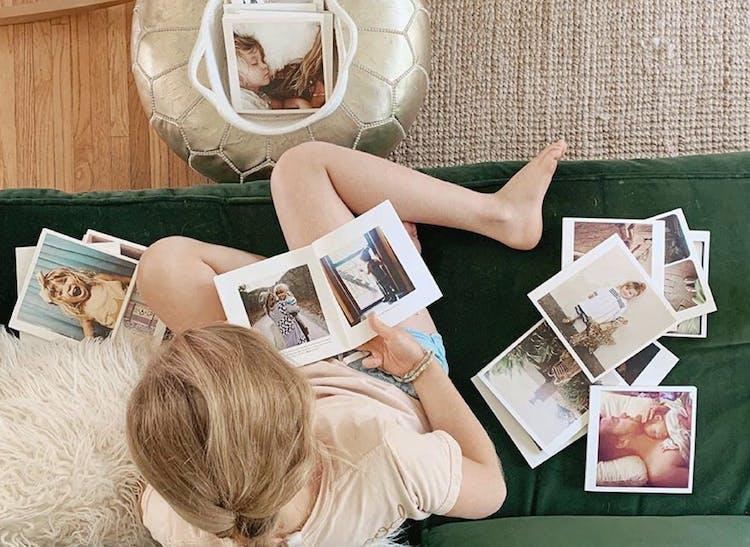 little girl flipping through Instagram photo books