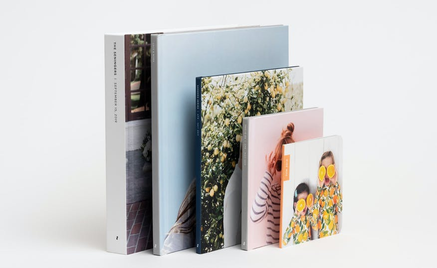 stack of hardcover and softcover photo books showing a family