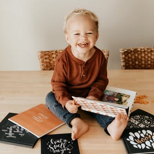 A little boy sits on a table and looks through Halloween Chatbooks