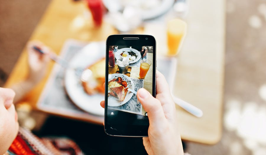 woman holding iPhone over dish taking photo of find with little boy watching