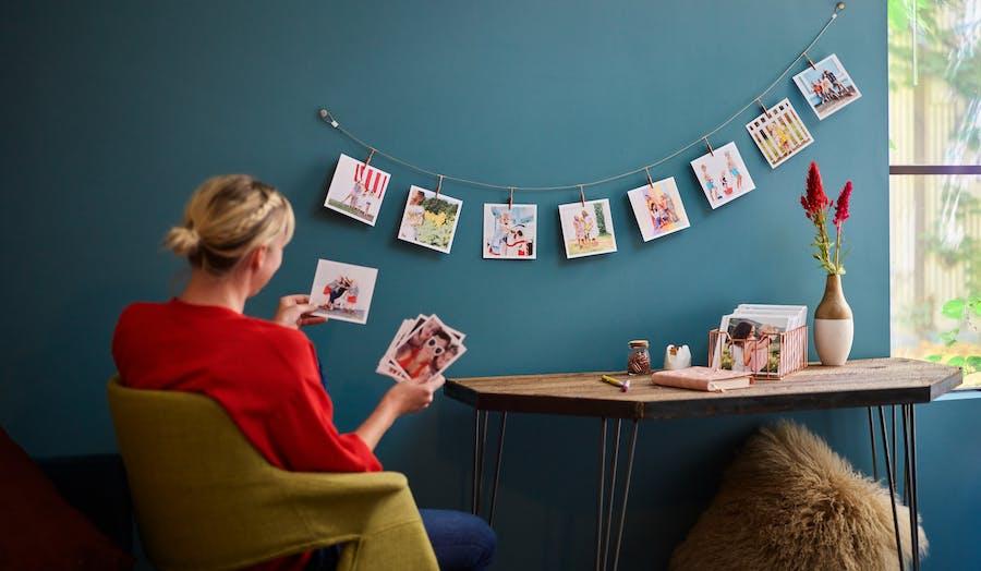 Woman at desk looking at Chatbooks photo prints