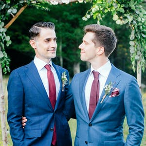 two grooms standing under dais on wedding day