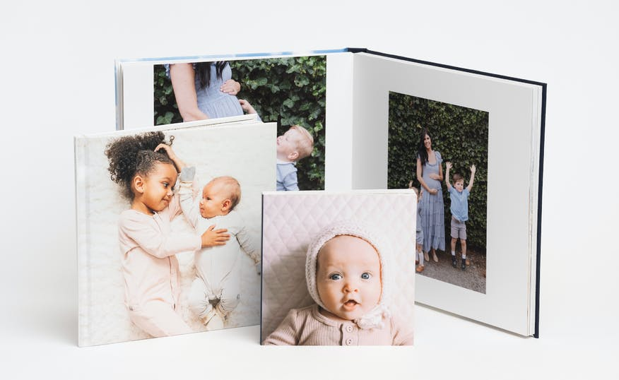 a collection of family photo books showing a baby on the cover and a family on premium pages