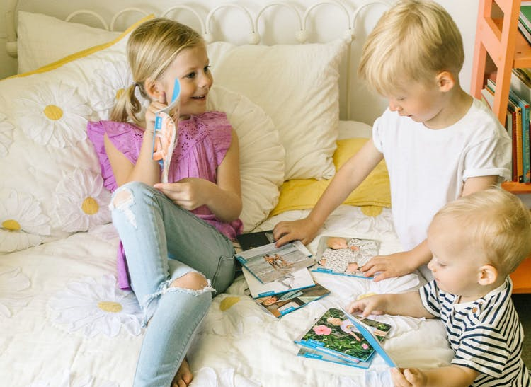 toddler and young girl looking at monthly family photo albums