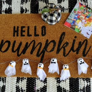 A hello pumpkin doormat with a homemade Halloween garland, pumpkin, and Chatbook on the mat.