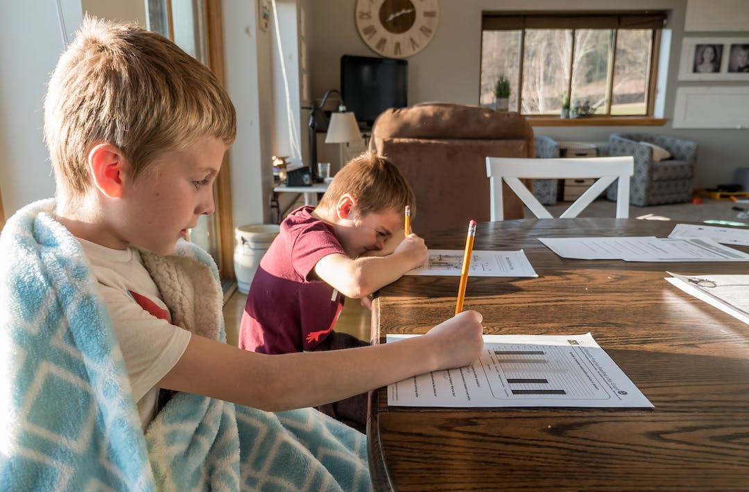 boys doing school work at kitchen table