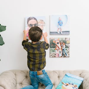 A little boy is hanging up family photos while standing on the couch