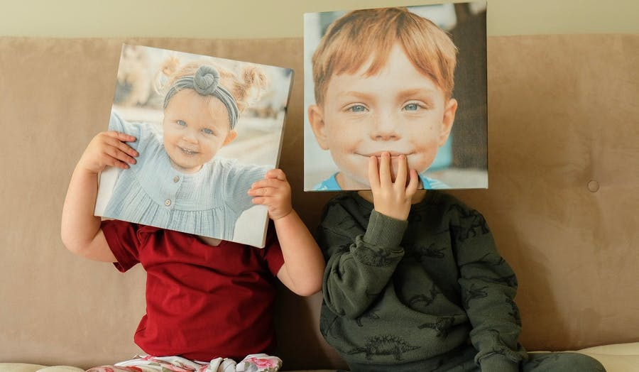 kids holding Chatbooks wall tiles up to their faces