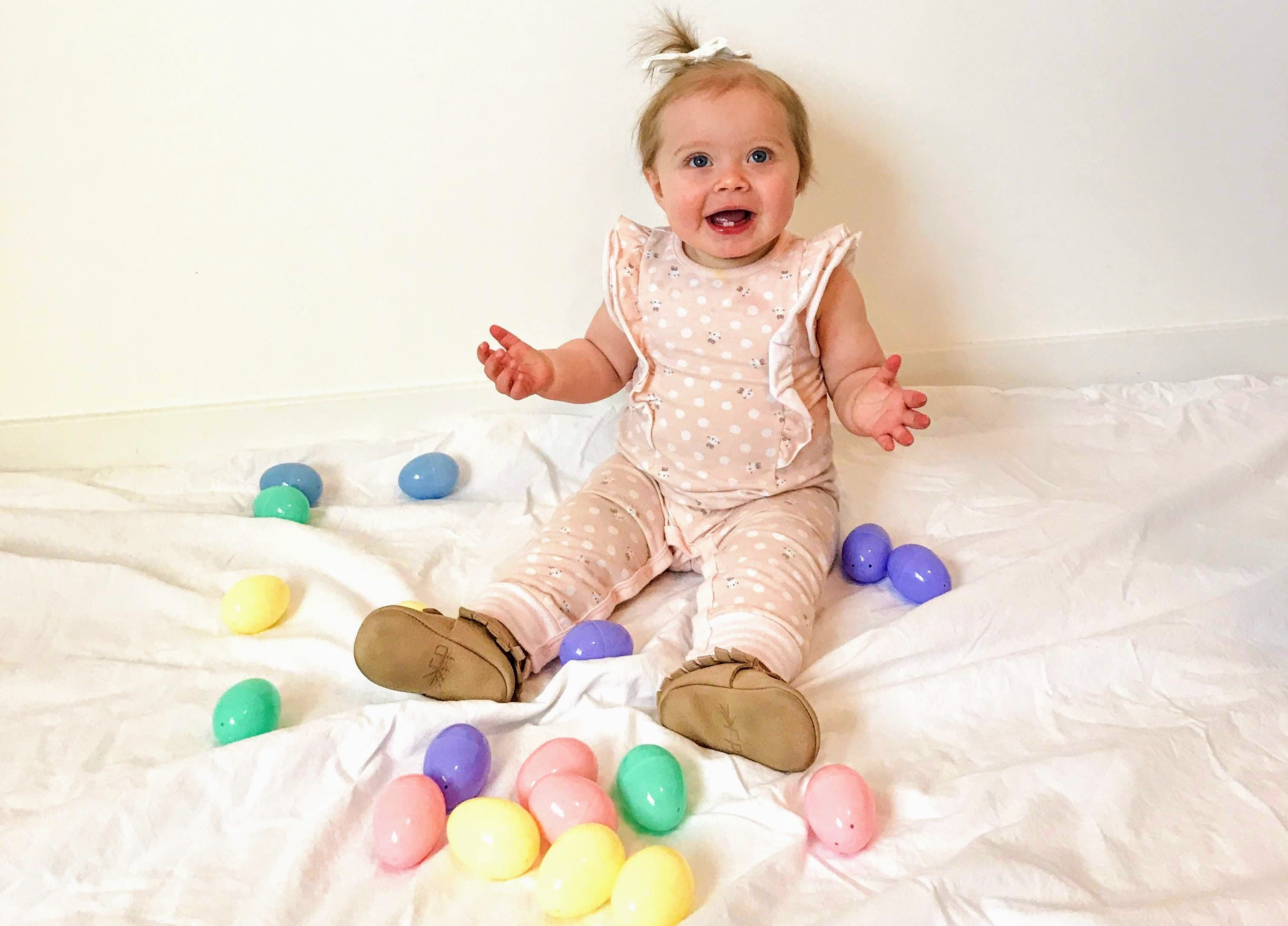 Infant surrounded by East eggs posing for photo