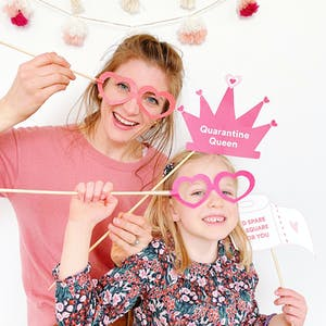mother and daughter playing with free photo booth props