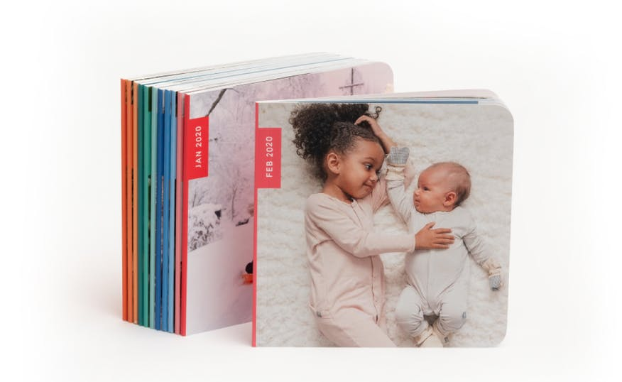 monthly photos book subscription book with two little girls on the cover and rainbow photo book spines