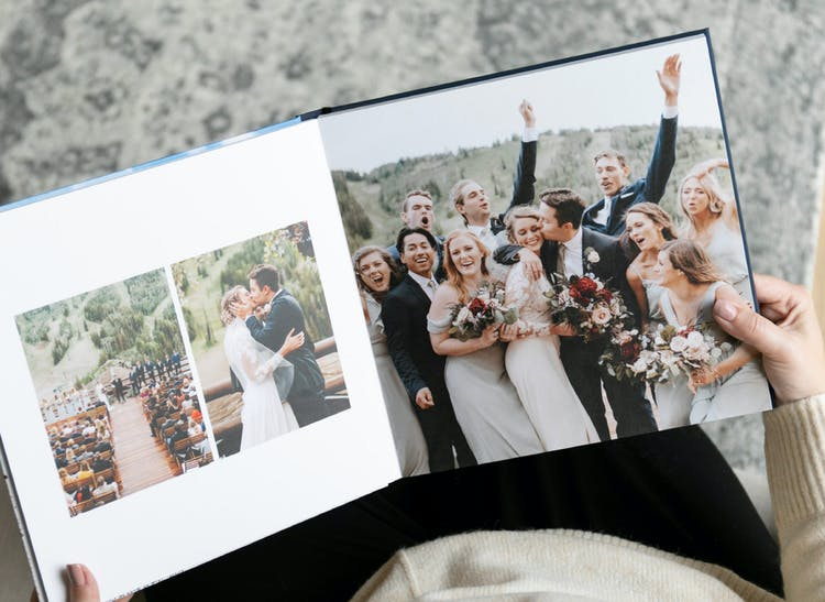 lay flat wedding album open showing bridal party with groom kissing bride