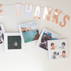 a banner saying give thanks surrounded by photos of families.