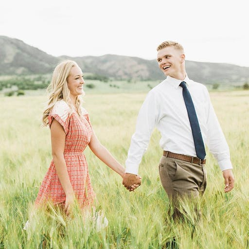 Couple holding hands in a field