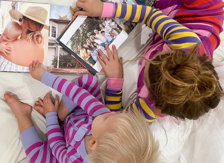 hardcover family photo books open on bed with kids flipping through them