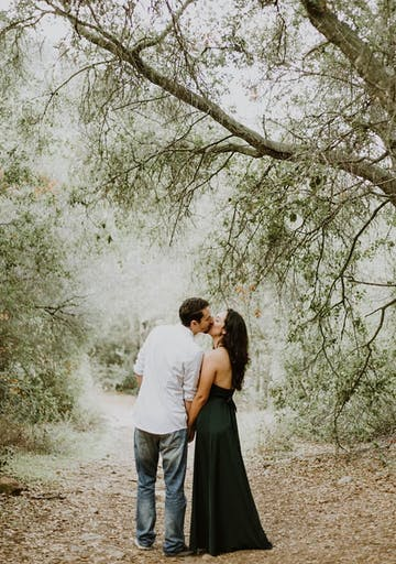 Couple kisses on a trail