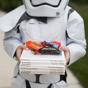 a child dressed up in Halloween costume with Chatbooks and candy in his hands