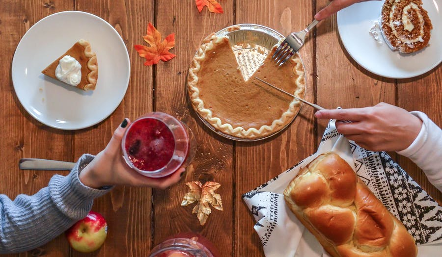 Thanksgiving photoshoot of pumpkin pie and leaves on a table