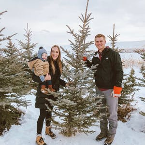 two parents and a toddler cutting their own Christmas tree in the snow