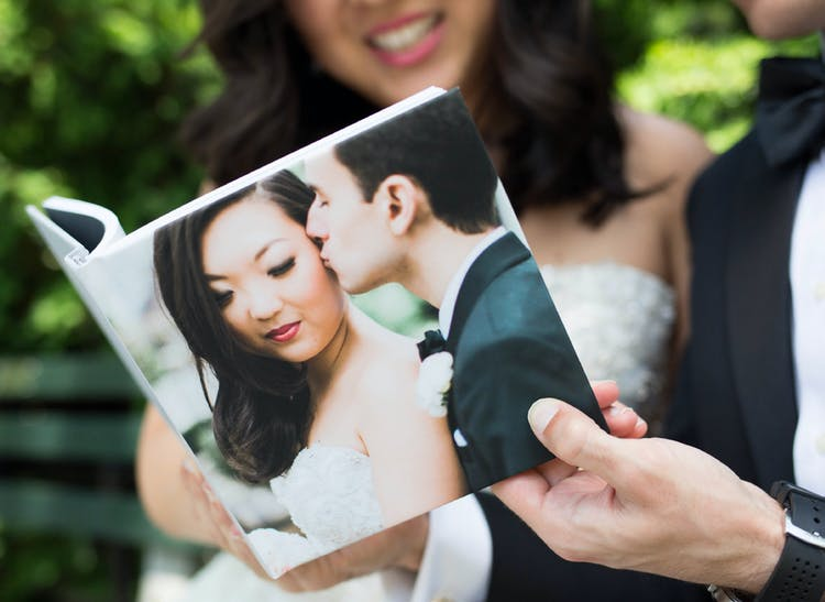 hand holding wedding photo album with groom kissing bride on hardcover
