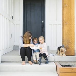 a mom, her 2 kids, and her dog all sit on the porch of their house and look through Chatbooks together.