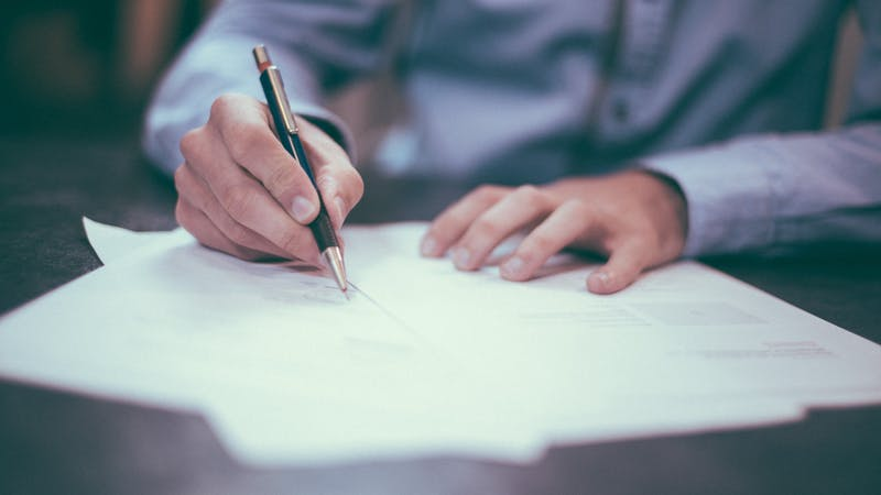 Image shows a man writing an examination