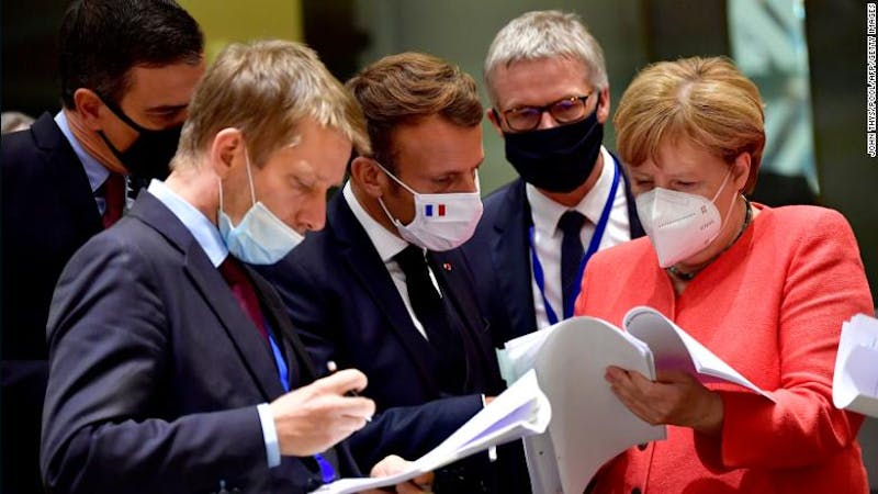 Spain's Prime Minister Pedro Sanchez (left), French President Emmanuel Macron (center) and German Chancellor Angela Merkel (right) looking at documents during the EU summit in Brussels on Monday.